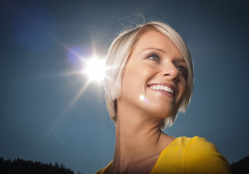 Kiss The Sun - a beautiful vivacious young blond woman has her cheek kissed by a bright sunburst as she laughs and smiles outdoors on a hot summer day against a clear blue sky, low angle view